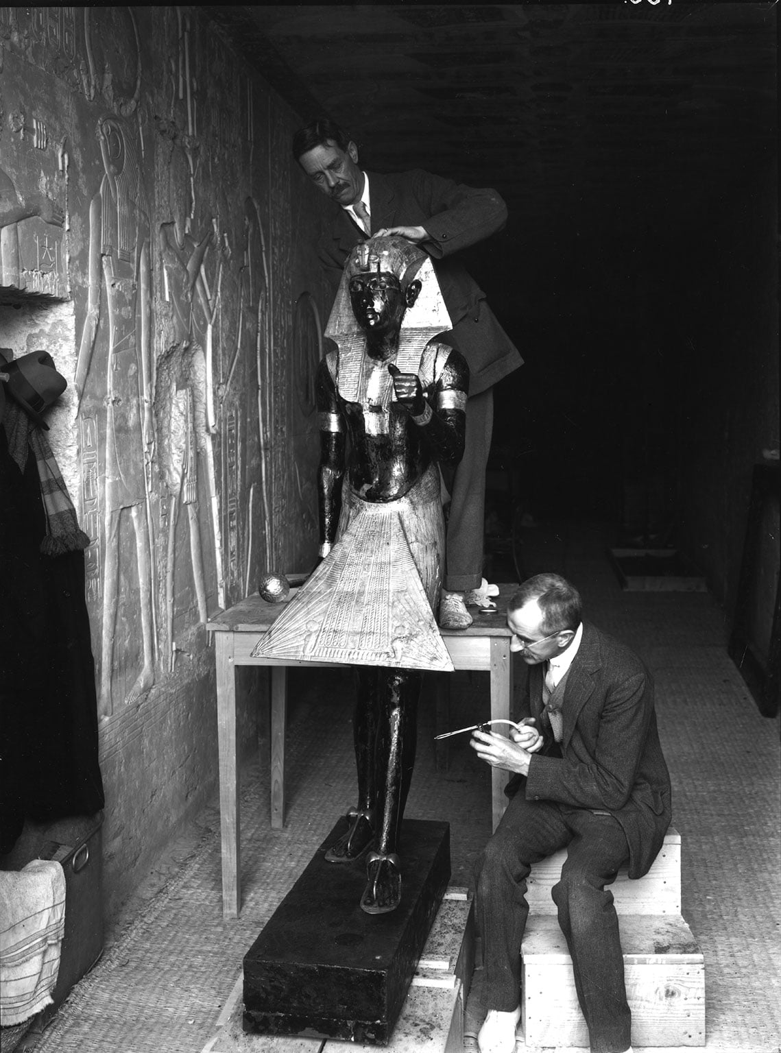 Arthur Mace and Alfred Lucas work on conserving a life-size statue of Tutankhamun that guarded the entrance to the king's burial chamber, Photo by Harry Burton, 1922