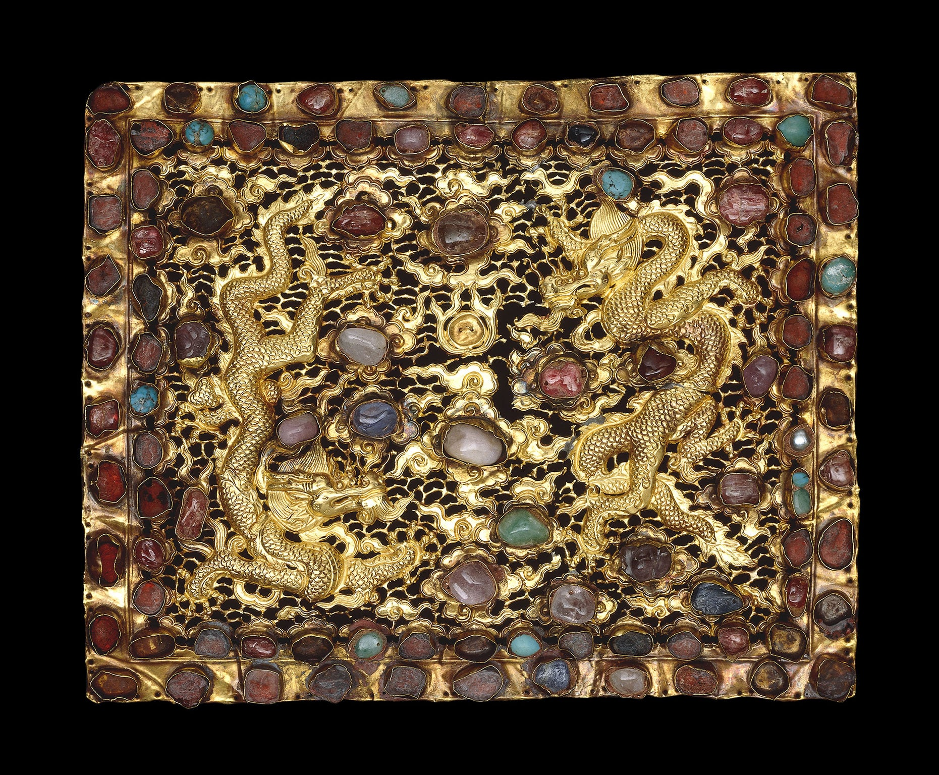 A pair of gold pillow ends, decorated with two dragons and worked in relief with chased detail and openwork. Gold, rubies, turquoise and other precious and semi-precious stones, Beijing or Nanjing, Xuande era, 1426-1435