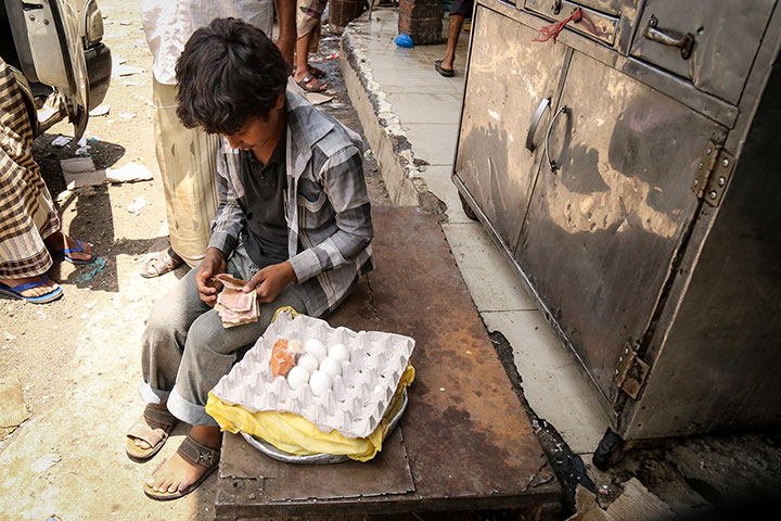 A child, impoverished due to the ongoing war in Yemen, counts his money he has made from selling boiled eggs. Yemen, Taiz City, Jamal Street, 3 September 2017