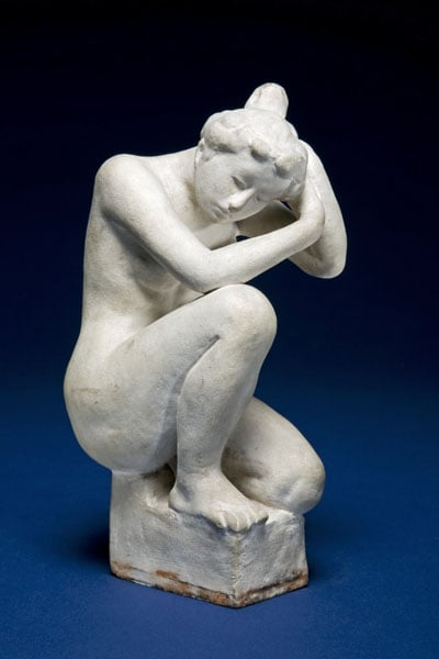 Figure of a crouching woman arranging her hair