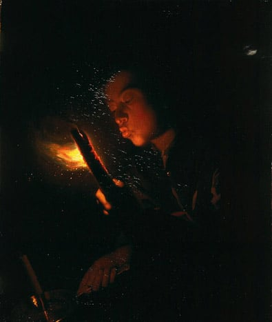 A Boy Blowing on a Firebrand to Light a Charcoal