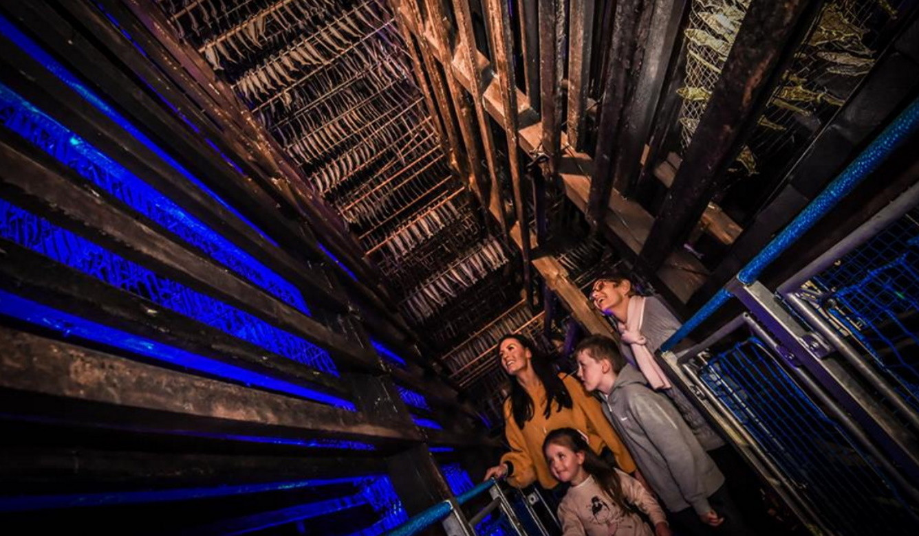 Family looking up into a herring smokehouse rafters filled with fake herring