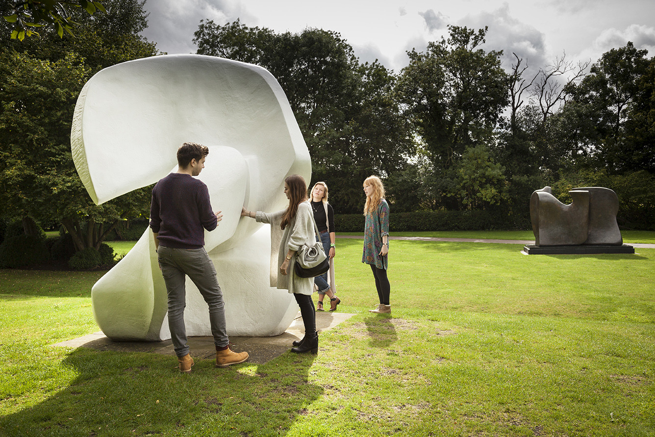 Three visitors looking at Henry Moore's 'Locking Piece'